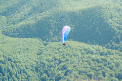 Paraglider in the sky over the green hills Stock Photo