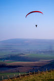 Paraglider in the sky, with red canapy, ladscape of fields belo Stock Photo