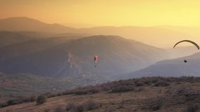 Paraglider Soaring Over The Mountains stock video footage