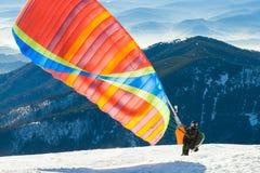 Paraglider som lanserar in i luft från det mycket bästa av en snöig berglutning Royaltyfria Bilder