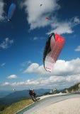 Paraglider som tar-av i fjällängarna Arkivfoto