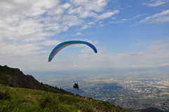Paraglider is starting off from the mountain. Tandem flight with paraplanner over the city stock photos