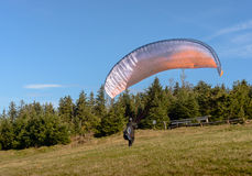 Paraglider starting. Parachute is filling with air in the mountains sunny day. Royalty Free Stock Photography