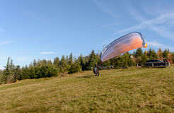 Paraglider starting. Parachute is filling with air in the mountains sunny day. Royalty Free Stock Photo