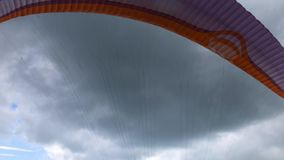 A paraglider starts flying over a mountain slope in tandem. A paraglider starts flying over a mountain slope in tandem against the sky with clouds stock video footage