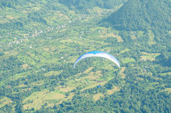 Paraglider on sunny day flight over the hills Stock Image