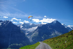 Paraglider in the Swiss Alps. Paraglider  on a dirt road in the Swiss Alps with mountain peaks in the background Royalty Free Stock Image