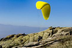 Paraglider takes off from mountain peak Royalty Free Stock Image