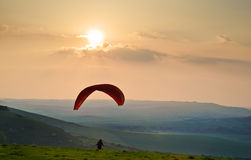 Paraglider takes off over countryside landscape Royalty Free Stock Photo