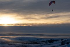 A Paraglider taking flight in the middle of winter against the sunset stock image