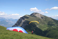 Paraglider Taking Off. A paraglider is taking off from a pasture high in the Italian Alps royalty free stock photography