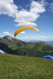 Paraglider Taking Off Italian Alp. Portrait view of paraglider taking off watched by another. Beautiful view of the Italian Alps is inviting us to take part royalty free stock images