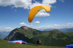 Paraglider Taking Off Italian Alp. Landscape view of paraglider taking off watched by another. Beautiful view of the Italian Alps is inviting us to take part stock photography