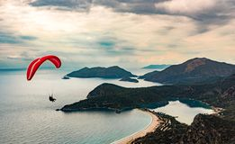 Paraglider tandem flying over the Oludeniz Beach and bay at idyllic atmosphere. Oludeniz, Fethiye, Turkey. Lycian way. Amazing Blue Lagoon detail. Summer and royalty free stock photography