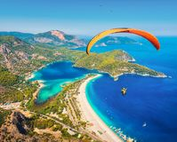 Paraglider tandem flying over sea with blue water and mountains Stock Photo