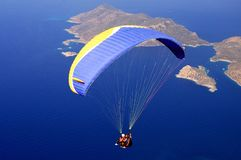 Paraglider tandem flying over the sea in Oludeniz, Turkey. Paraglider tandem flying over the sea with blue water in Oludeniz, Turkey stock photos