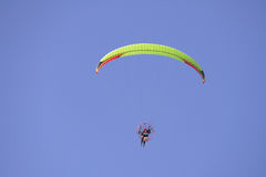 Paraglider. A very colorful motorized paraglider high in the bright blue sky Stock Photo