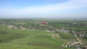 Paraglider zdejmuje od zielonego wzgórza Widok pola, niebieskie niebo w chmurach i różni domy, zbiory wideo
