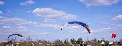 Paraglideren flyger mot bakgrunden av fält, land ovanf?r sikt paragliding arkivfoton