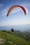 Paraglideren hoppar från berget till havet, blå himmel, värme bris, en hoppa fallskärm, arkivbilder