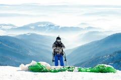 Paraglideren i hjälmen som förbereder sig att få, lanserade från snöig lutning av ett berg Arkivbilder