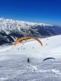 paraglideren med instruktören över skidar lutningar fotografering för bildbyråer