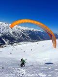 paraglideren med instruktören över skidar lutningar arkivfoto