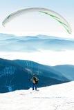 Paraglideren som förbereder sig att få, lanserade från snöig lutning av ett berg Arkivbilder