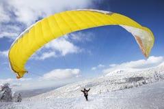 Paraglideren startar att flyga från överkanten av snöberget arkivbilder