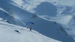 Paraglideren startar att flyga i bergen som skidar på en lutning mot bakgrunden av en liten regnbågeeffekt, Les välvar royaltyfria foton