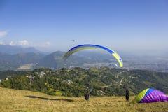paraglideren tar p? en bl?tt hoppa fallsk?rm av fr?n en backe mot bakgrunden av en stad i en gr?n bergdal royaltyfri foto