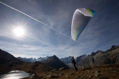 Paragliderpiloten står på en lutning och balanserar hans paraglider ovanför hans huvud i fjällängarna av Schweiz arkivfoto