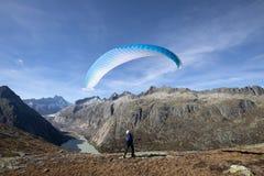 Paragliderpiloten står på vaggar och balanserar hans paraglider ovanför hans huvud nära sjön Grimsel i de schweiziska fjällängarn royaltyfri bild