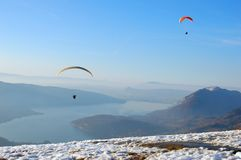 Paraglider flying over the lake Stock Photography