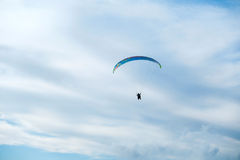 Paragliders in bright blue sky, tandem of instructor and beginner.  Royalty Free Stock Images