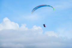 Paragliders in bright blue sky, tandem of instructor and beginner.  Royalty Free Stock Image