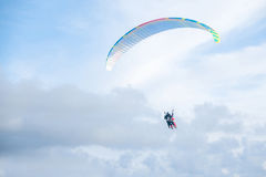Paragliders in bright blue sky, tandem of instructor and beginner.  Royalty Free Stock Photo