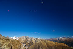 Paragliders enjoying majestic view to Swiss Alps from the top of Stock Photo