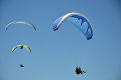 Paragliders in flight in blue sky stock photography