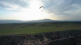 Paragliders fly over amazing mountain range during paragliding extreme sport competition. Paragliders fly in the