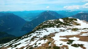 Aerial panoramic view of a flying paraglider of white colors parachutes from the snowy mountains in Austria. Beautiful views in th stock footage