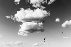 Some paragliders flying against a beautiful. deep sky, with big white clouds. Paragliders flying against a beautiful deep sky, with big white clouds royalty free stock image