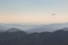Paragliders flying over mountains Stock Photo
