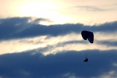 Paragliders flying on the wing against the sun in the clouds Royalty Free Stock Images