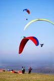 Paragliders i himlen och på jordningen med röd och gul ca Royaltyfria Bilder