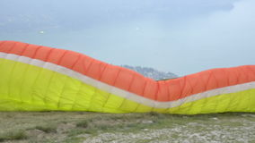 Paragliders landing and taking off from mountain slope near Locarno stock footage