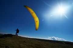 Yellow paraglider sun sky grass royalty free stock image