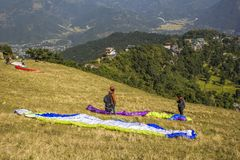 Paragliders na zbocze góry przygotowywają zdejmować na tle zielone góry i domy wewnątrz fotografia royalty free