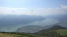 Paragliders que aterram e que descolam da inclinação de montanha perto de Locarno filme