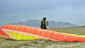 Paragliders que aterram e que descolam da inclinação de montanha perto de Locarno video estoque